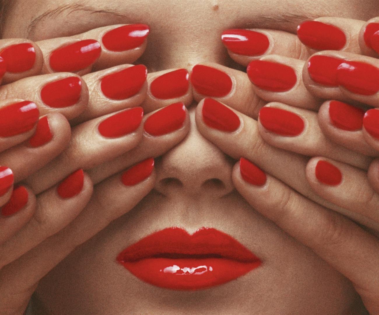 Modefotografie-Legende Guy Bourdin hatte scheinbar auch eine Schwäche für erbeerrote Fingernägel. Seine Fotografie zeigt dreißig rot lackierte Fingernägel, die nur die stark geschminkten Lippen des Models preisgeben