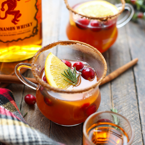 This recipe for a healthier holiday Hot Toddy is amazing! The cinnamon whiskey mixed with apple cider and citrus makes the perfect holiday cocktail!