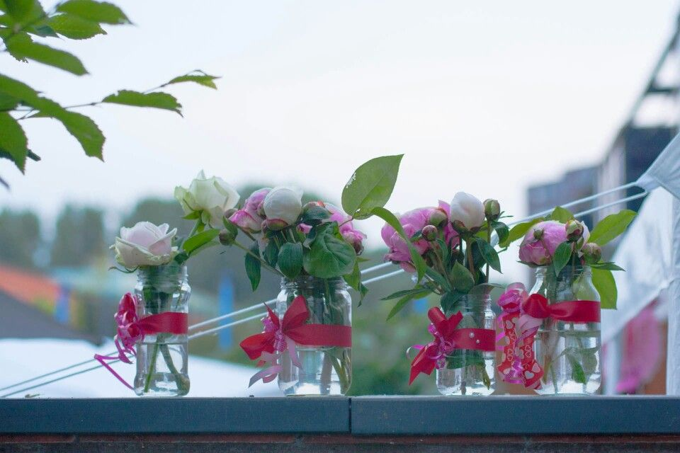 Saved up jars with ribbons and fresh pink and white flowers.