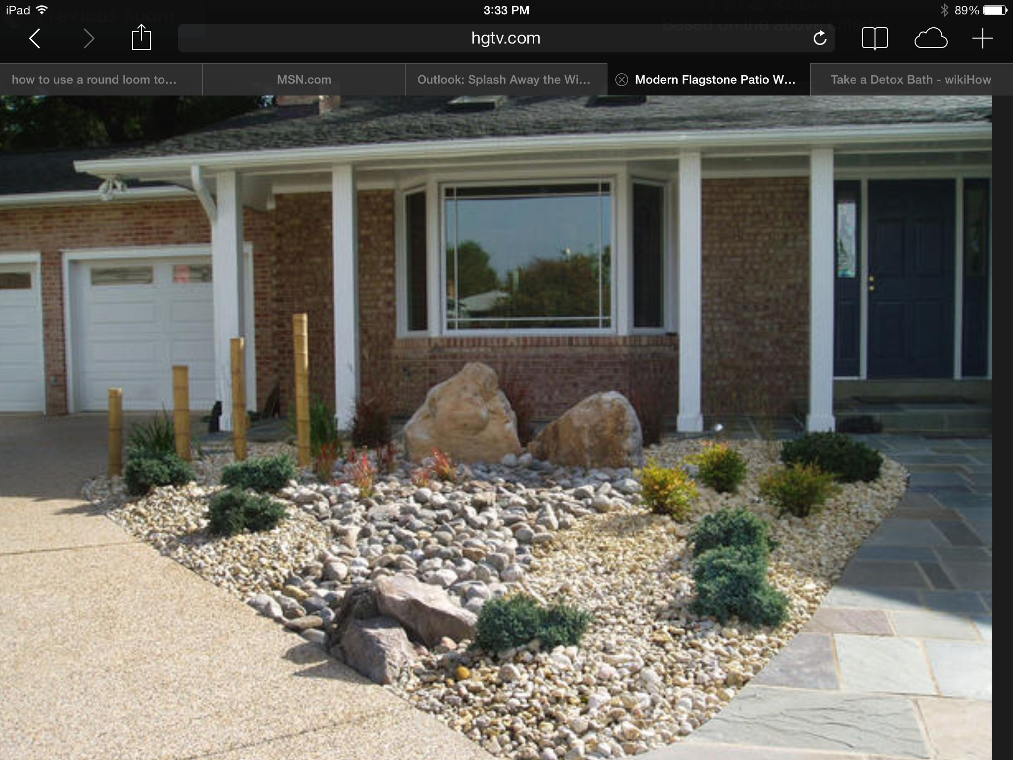 a triangular plot between the driveway and front walkway is decorated with rock gravel and ornamental shrubs four bamboo canes each smaller than the one