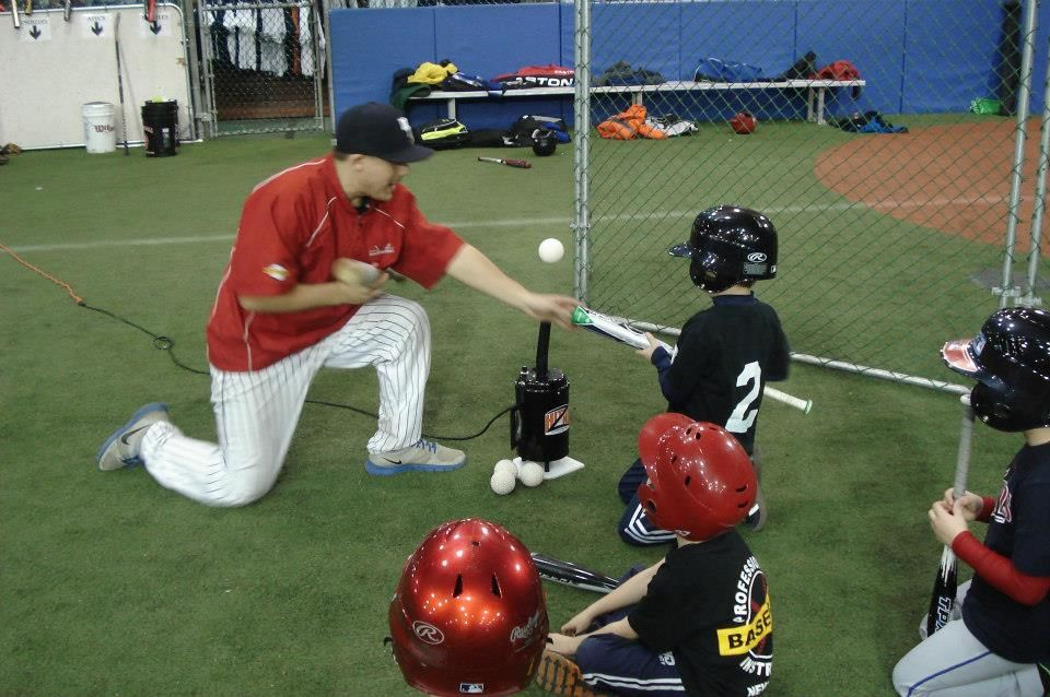 Coach Zak Rose working with Christmas at PBI Campers off of the HitZone tee - a tee that holds the ball in the air; December 2013