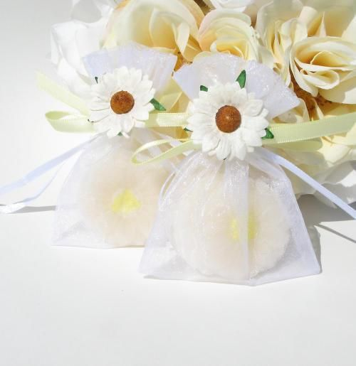 Daisy Soap Wedding Favor Set includes three guest soaps in the shape of a daisy complete with a yellow center and white petals. They have a lovely vanilla scent. They come packaged in a white organza bag. It is tied closed with a yellow satin ribbon and a daisy flower accent.