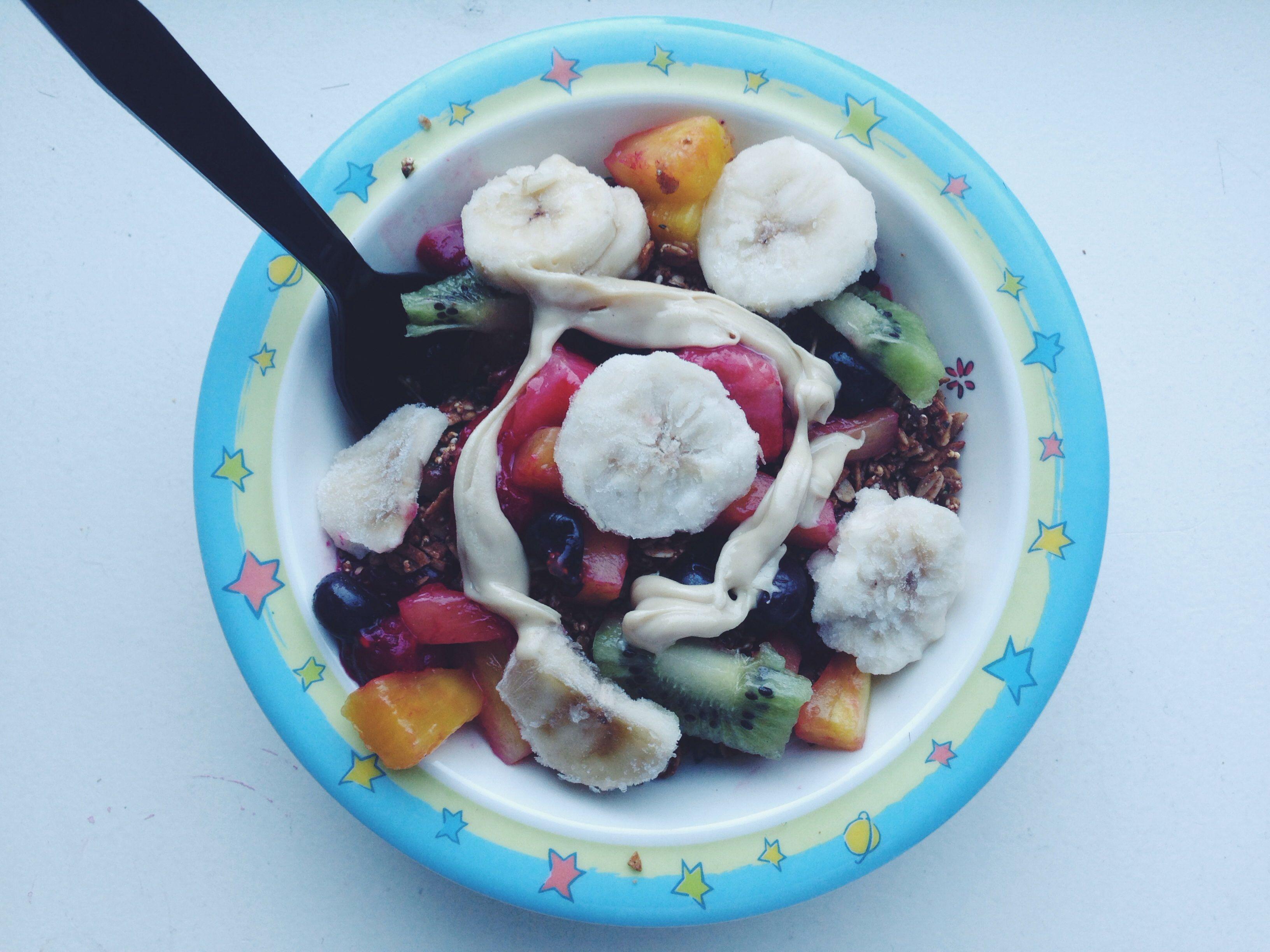 My Friday breakfast. -- 1/3 cup blueberry hemp Purely Elizabeth granola, some plain SoDelicious coconut yogurt, a kiwi, mixed berries, some frozen banana slices and a tbsp of Artisana cashew butter. #dairyfree #vegan #glutenfree