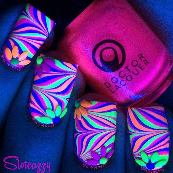 Adorable looking glow nail polish design. Paint on glow in the dark nail polish in various colors and design them to look like warping lines of colors passing through the nails. The flower petals on top of the nail polish add to the overall cuteness of the design.