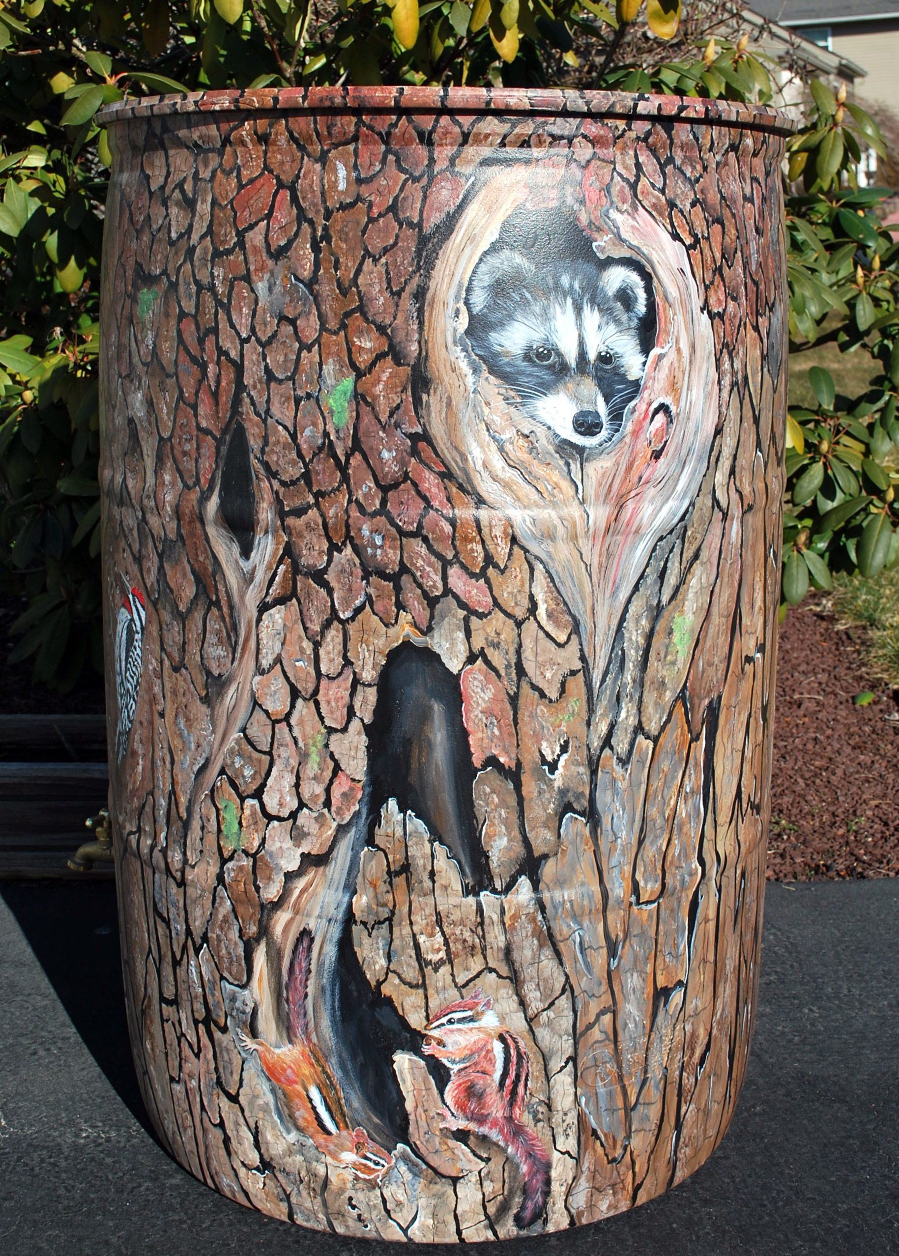 50 gallon rain barrel painted as a tree trunk with birds