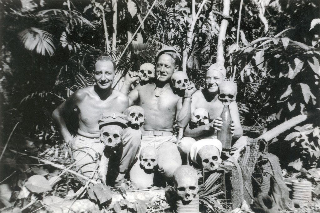 U.S. Naval personnel posing with the remains of a Japanese encampment.