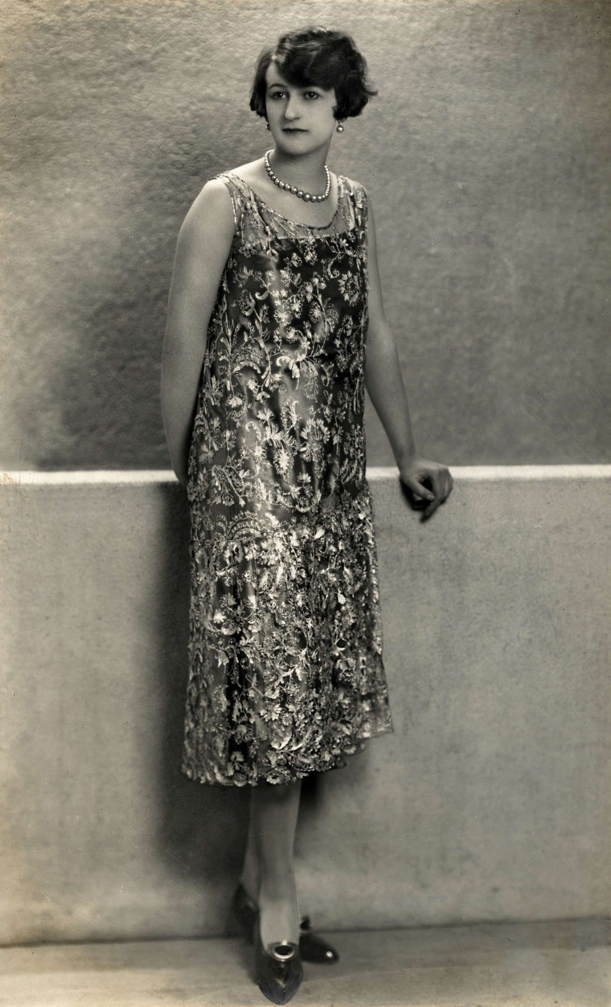 Women's Fashion. Creation from the spring fashion 1925: a sleeveless gown with rich lace on a slippery surface. [Paris, France], 1925.