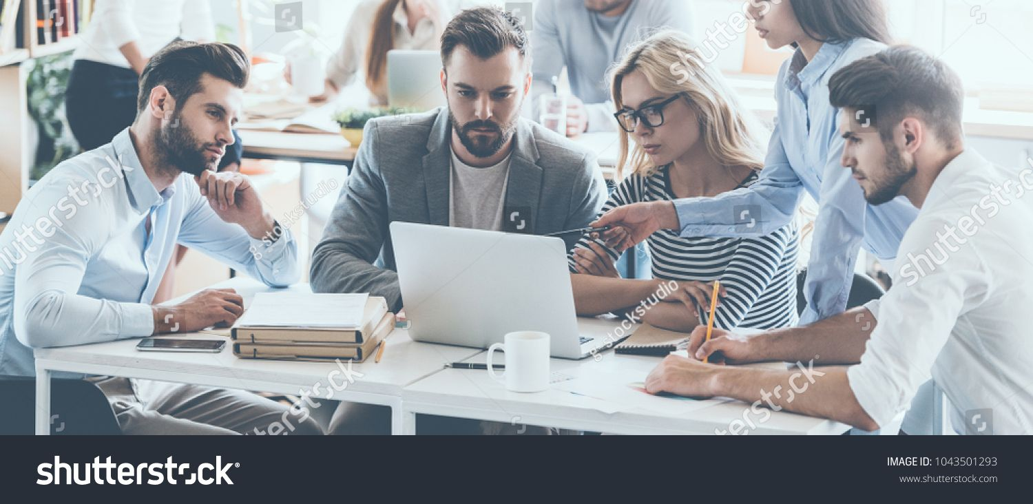Full concentration at work. Group of young business people working and  communicating while sitting… | Business stock photos, Financial health,  Business stock images