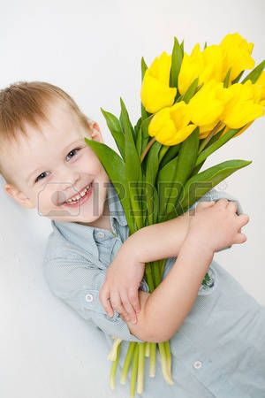 portrait of Smiling boy with a bouquet of yellow tulips flowers in hands standing near white wall