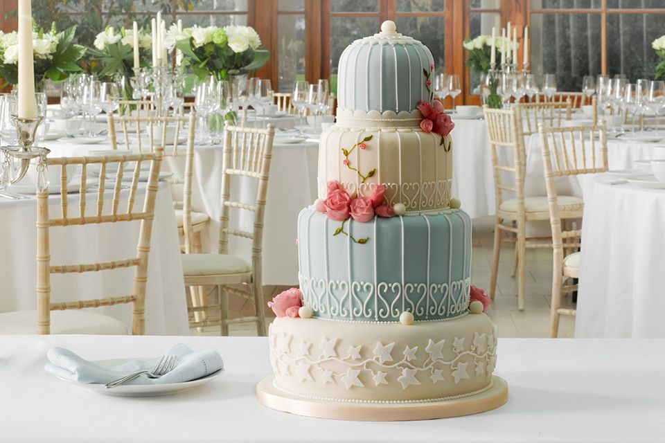 Four tier pale blue & white Birdcage Marks & Spencer wedding cake decorated with fresh flowers
