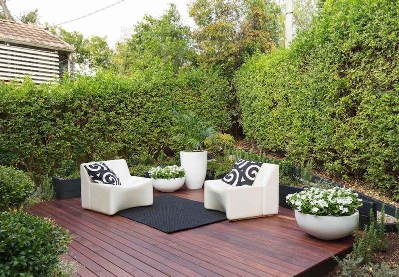 terrasse en bois avec salon de jardin et vegetation abondante en tant que brise vue