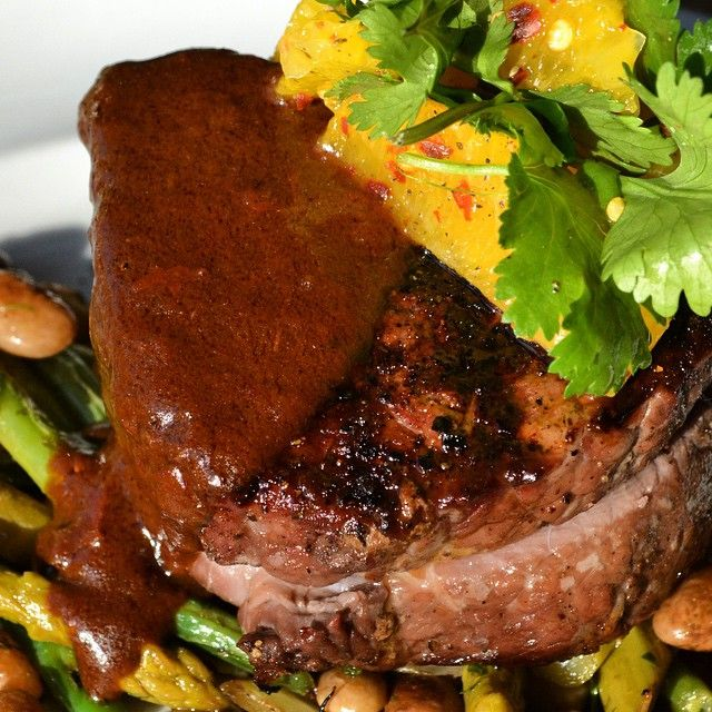 "Grilled top sirloin, smothered in an ""ancho mole"" demi. Served on a bed of pinto beans, topped with escabeche ratatouille and citrus salsa."