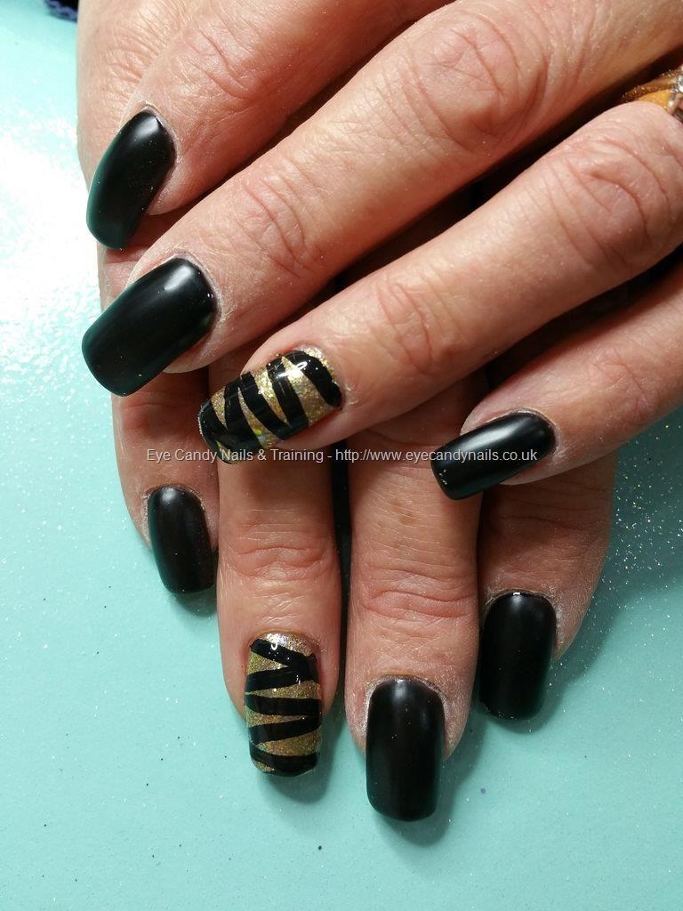 Matte black polish with gold glitter and ribbon effect nail art ...