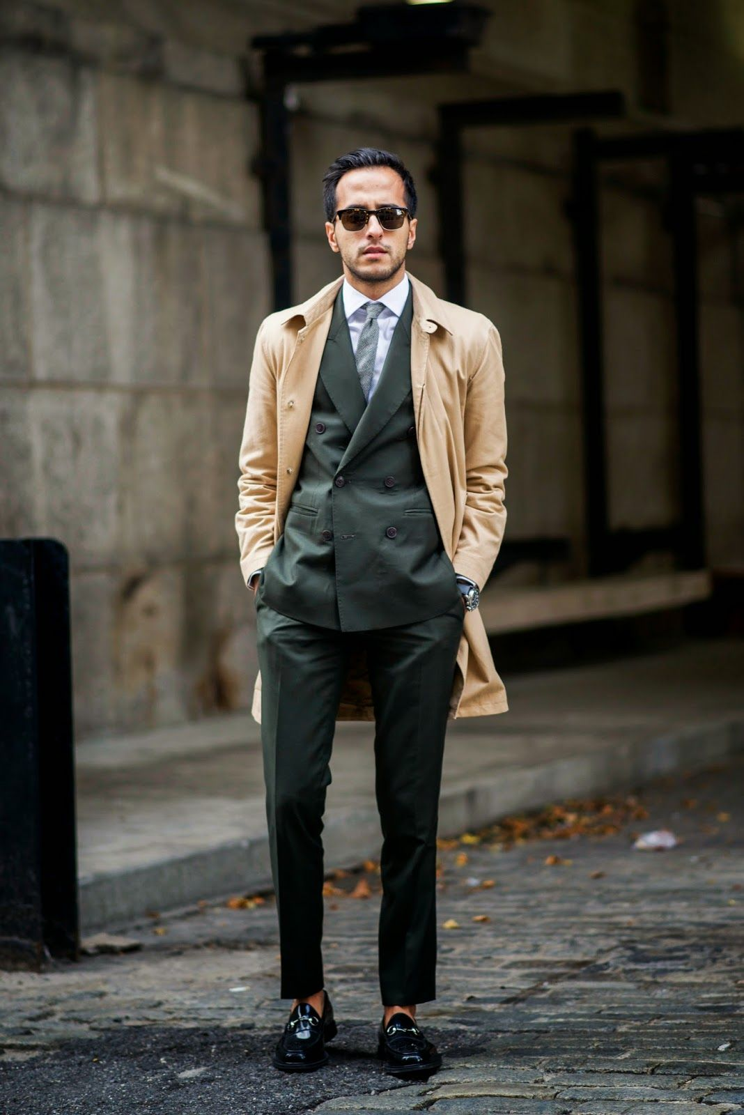 Dapper mens forest green suit and slim gray necktie and camel overcoat