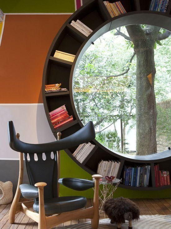 This slotted bookshelf doubles as framing for a circular window.