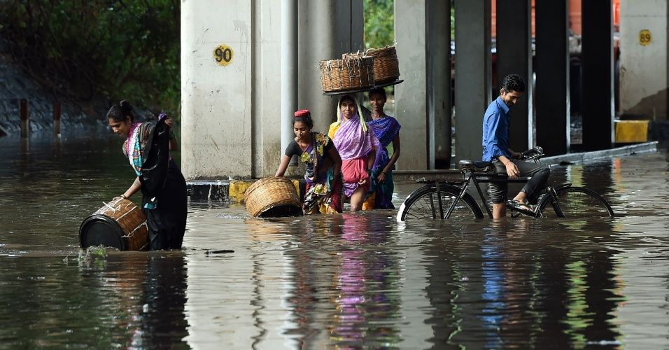 Pedestres e um ciclista tentam atravessar avenida alagada de Mumbai, na Índia, que sofre as consequências de um temporal que atingiu a cidade nos últimos dias