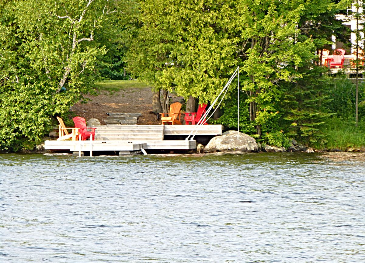 "This ""cottage "" has south-west exposure and a flat level lot allowing you to be close to the water for swimming or just lounging on the sunny dock.   The large deck allows you to sit and view the most beautiful sunsets. There is a large hot tub; gas BBQ, landscaped fire pit, area to play volley ball and badminton or any other sport."