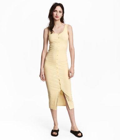 Hellgelb. Wadenlanges Trägerkleid aus festem Rippenjersey. Das Kleid hat oben und unten funktionelle Druckknöpfe und dazwischen Zierdruckknöpfe.