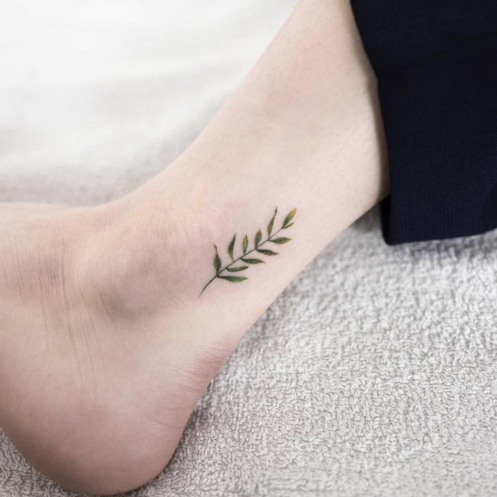 Minimalist leaf tattoo on the ankle.