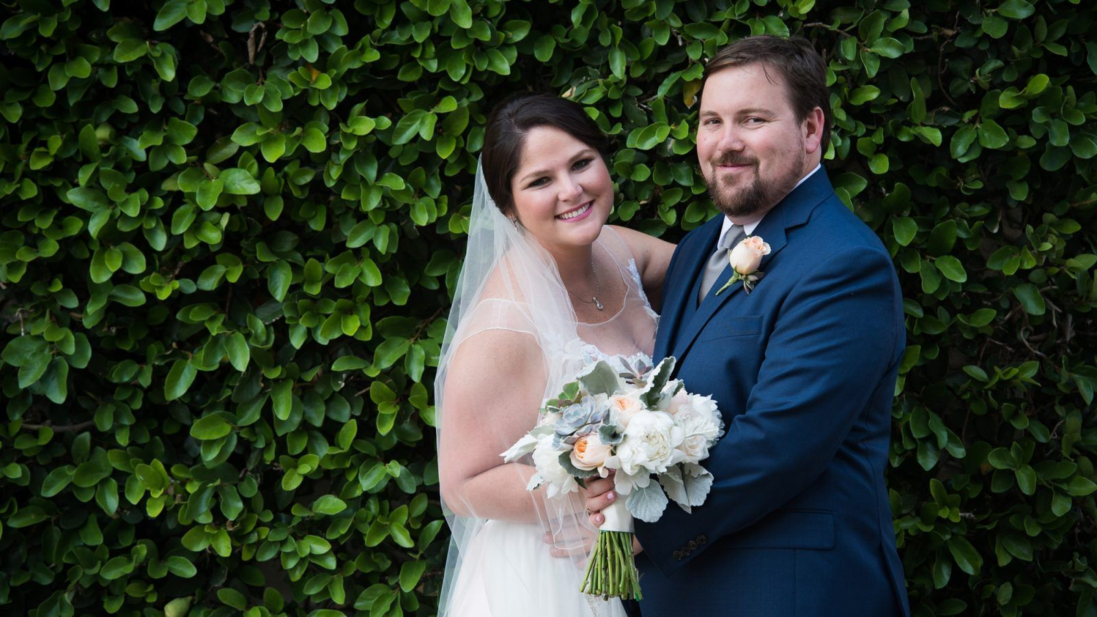 Bride and groom in front of an ivy wall in historic St Augustine ...