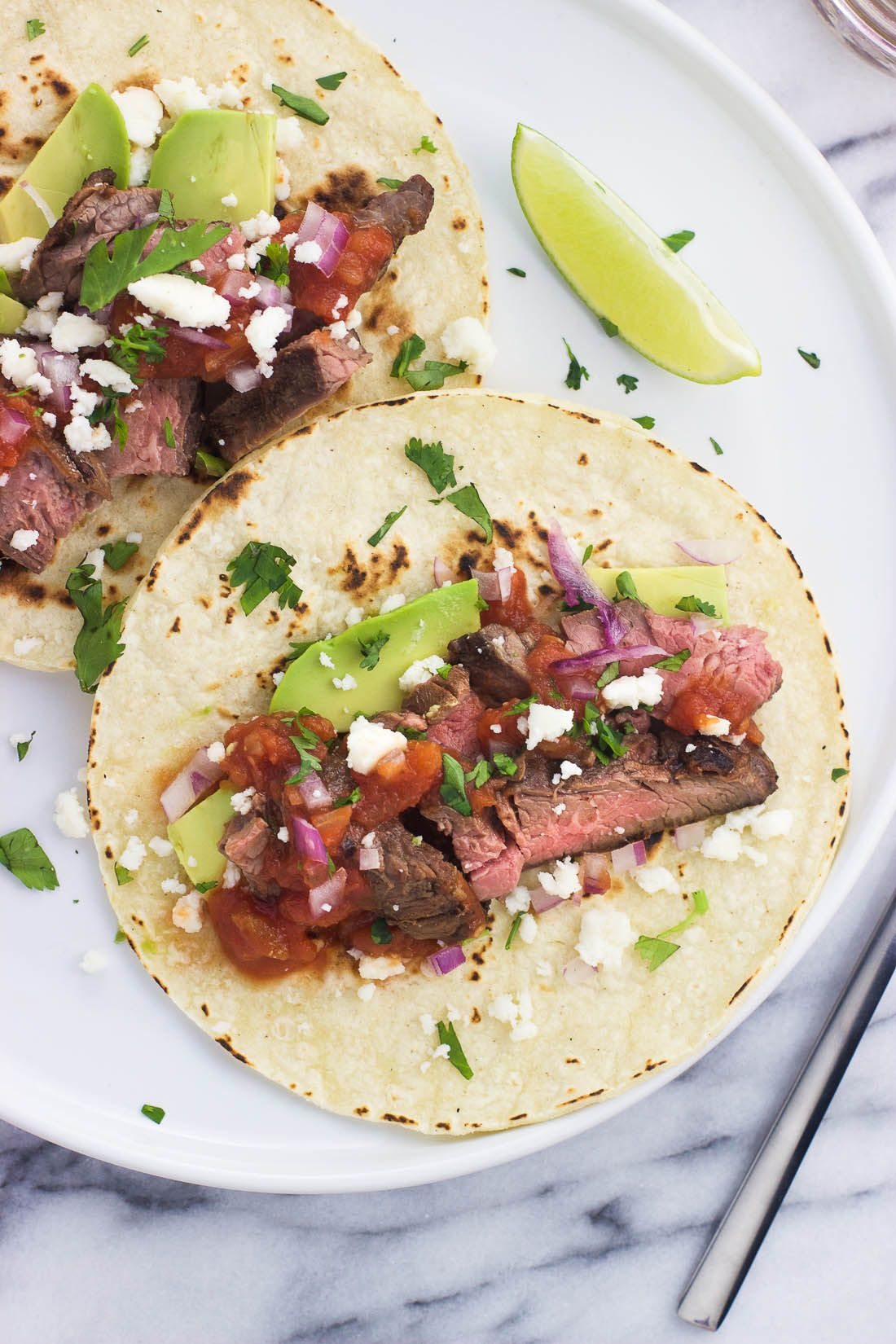 Carne asada tacos feature tender grilled skirt or flank steak in the BEST carne asada marinade. Serve them alongside a plethora of your favorite taco toppings and spice up taco night! #asadatacos