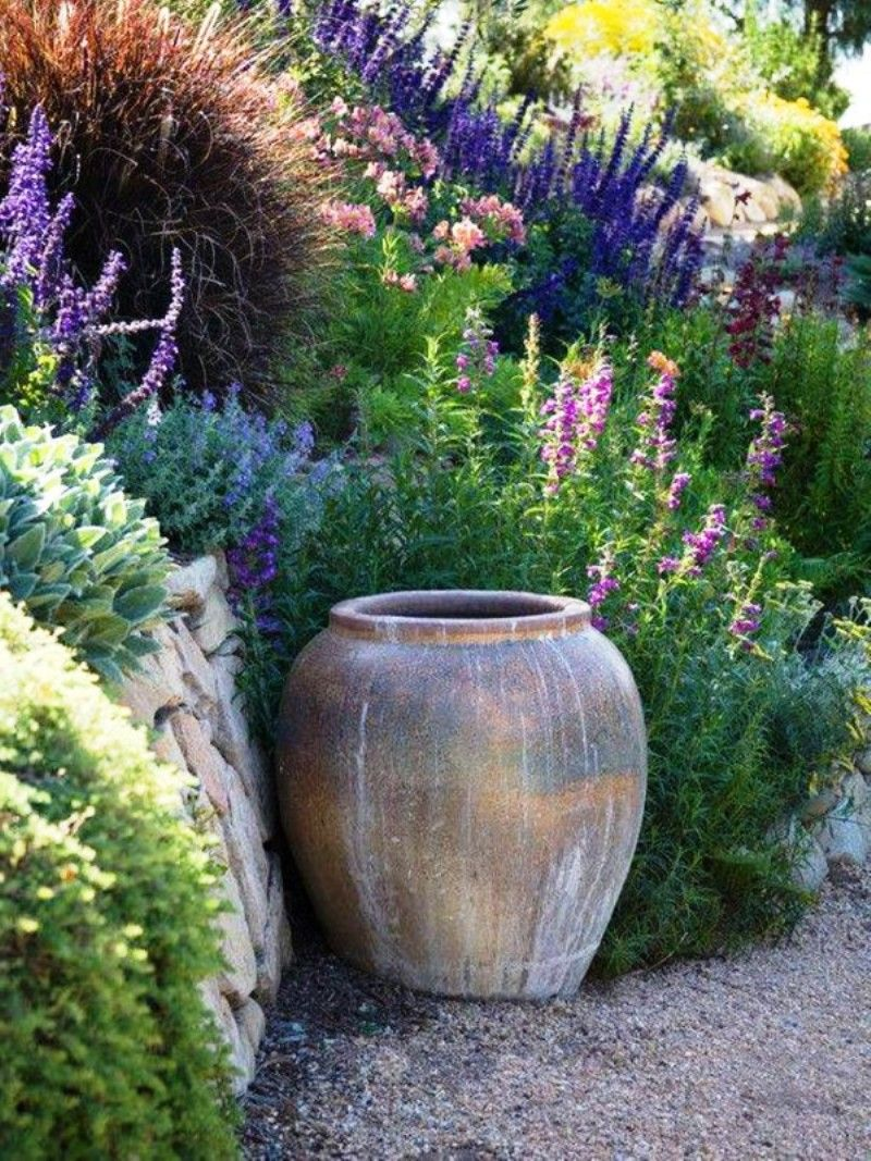 love landscape with pottery, grasses, and wild flowers. purple is