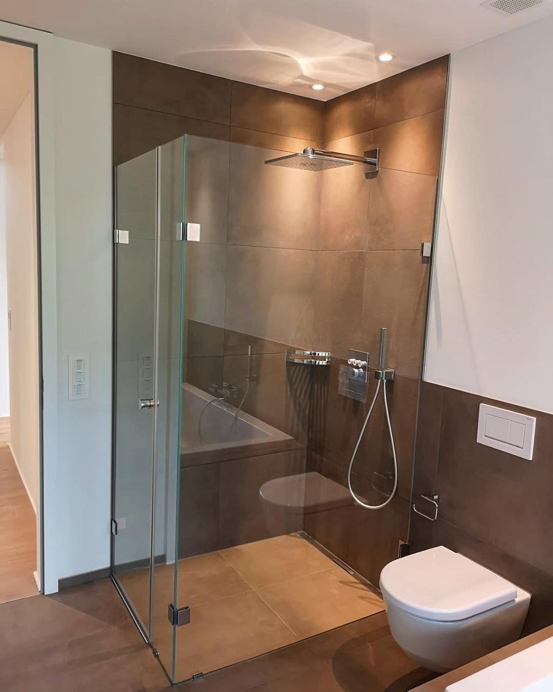 Badezimmer in warmen Brauntönen mit eleganter ebenerdiger Dusche