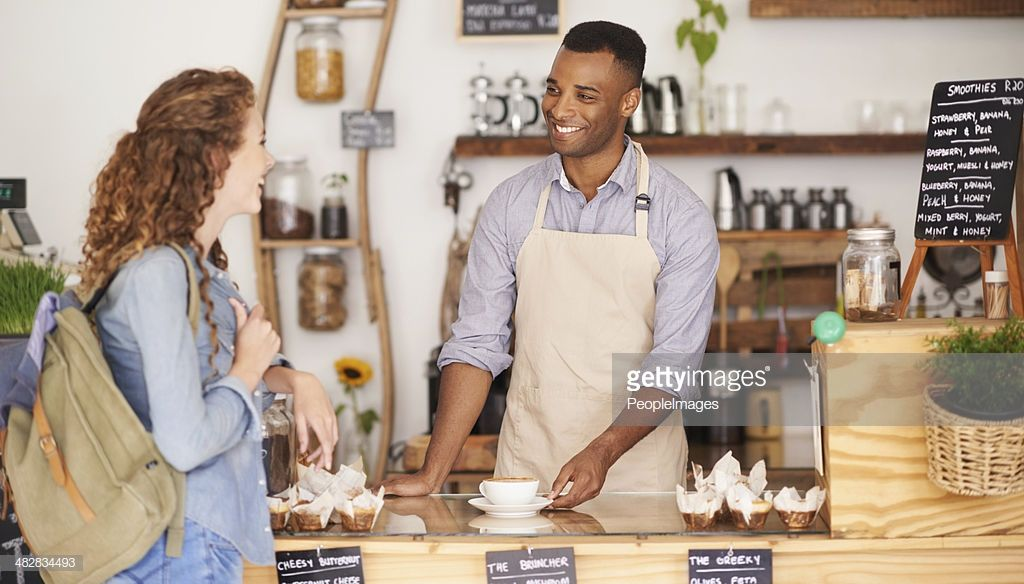 Cropped shot of a handsome young barista serving a female
