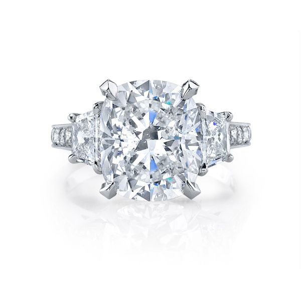 Rose is a custom three stones engagement ring set with a Cushion cut diamond in Platinum and one row of diamonds on the band. #cushiondiamond #cushioncut #diamondring #engagementring #threestonesetting