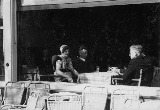 Afbeelding van enkele mensen aan een tafeltje voor het open raam in mogelijk het Haagsche Koffiehuis (Vredenburg 28) te Utrecht. 1942  #Utrecht #Spakenburg