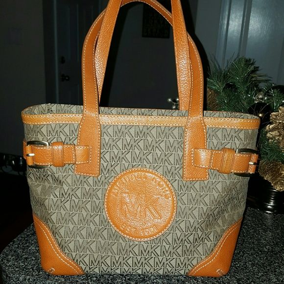 100% AUTHENTIC MICHAEL KORS MILLBROOK TOTE Soooo cute! Brown MK logo with orange leather detail. Antique gold hardware.  13x9x5. 8 inch strap. Beige canvas interior.  Multi pockets all functional no rips or tears. Only mark is on bottom of bag as seen in pic!!! Michael Kors Bags Totes