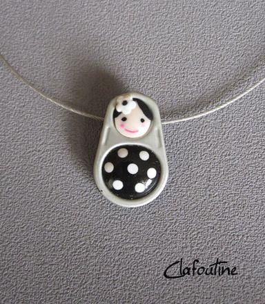 Un petit pendentif original: une poupée russe noire et petits pois blancs / matriochkas