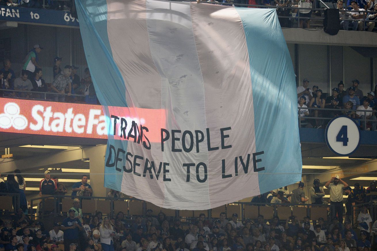 Fans unfurl trans people deserve to live banner during