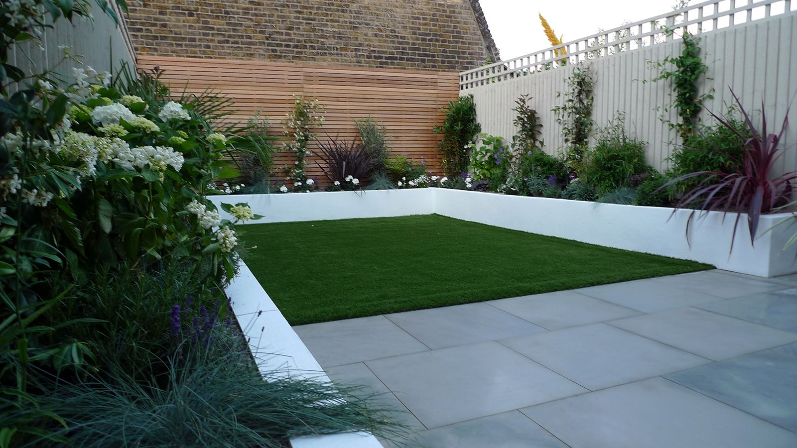 Sawn grey sandstone paving raised rendered beds hardwood screen painted stone fence london small - Garden ideas london ...