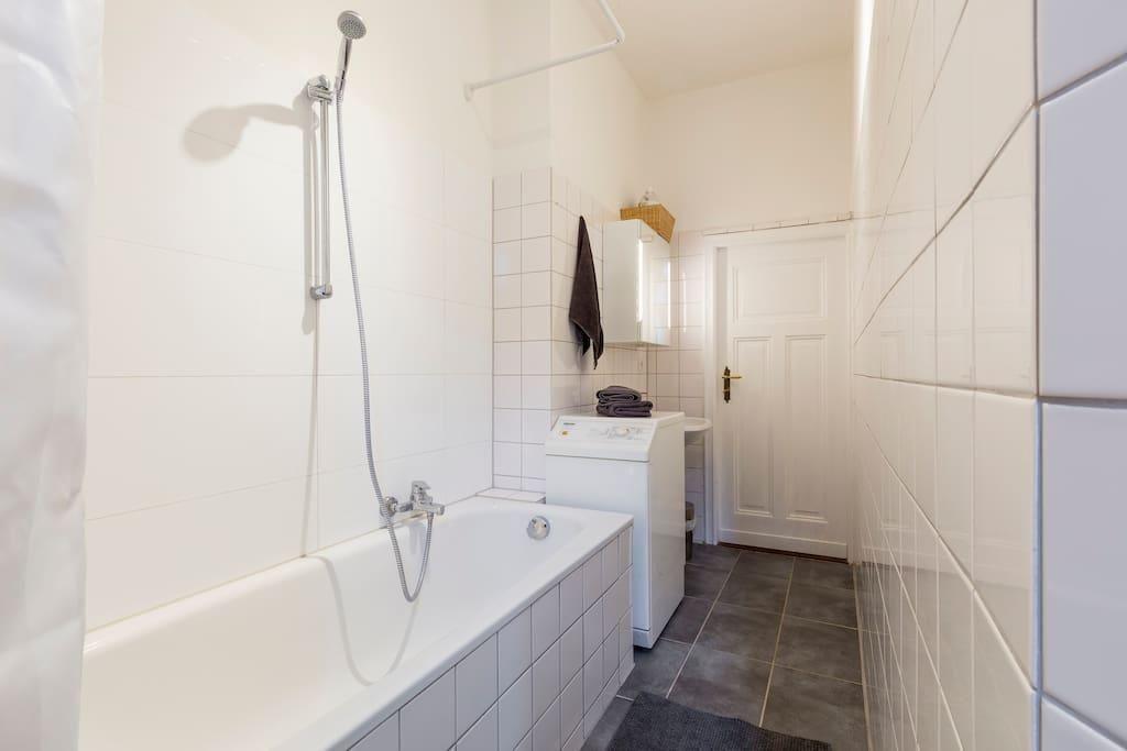 Badezimmer mit dunklem Fliesenboden, Badewanne und schöner Holztüre - badezimmer badewanne dusche