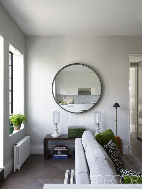 A custom-made bronze mirror from Wyeth hangs above an antique bench found at Christie's in the living room; the floor lamp is from Galerie des Lampes.