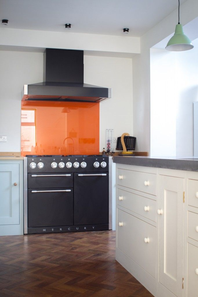 Kitchen With A Central Island Topped In Concrete With Orange Glass  Spalshback Over The Range Cooker
