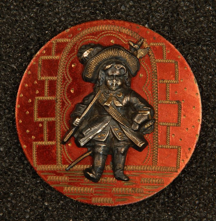 THE LITTLE COLONEL BUTTON. Large 1-piece brass etched with bricks and archway, tinted red and laquered, with silvered brass escutcheon of the character from Annie Fellows Johnston's novel. 1 3/8. Robinson Button Collection Collector Note: Wonderful original tint!