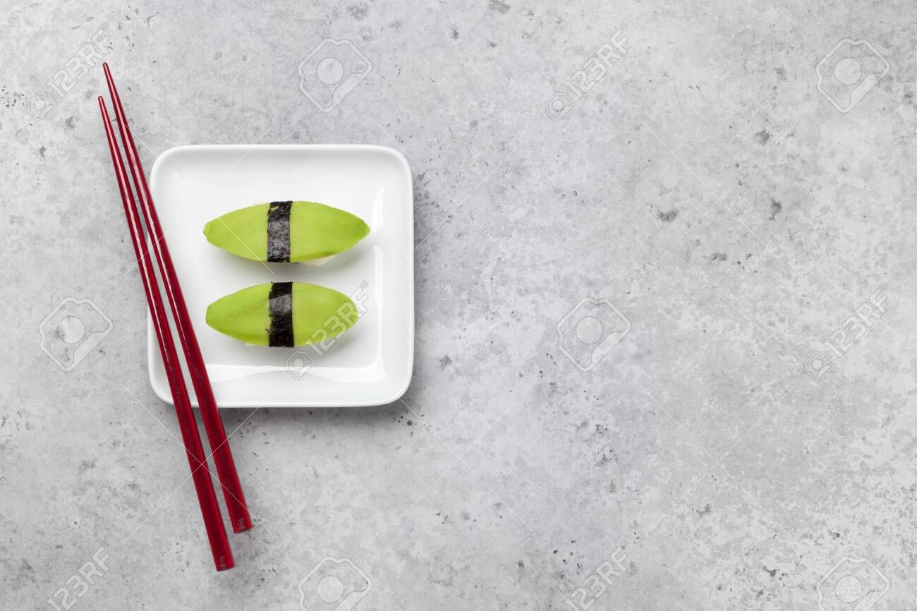 Japanese sushi set with avocado. On plate over stone background with space for text ,