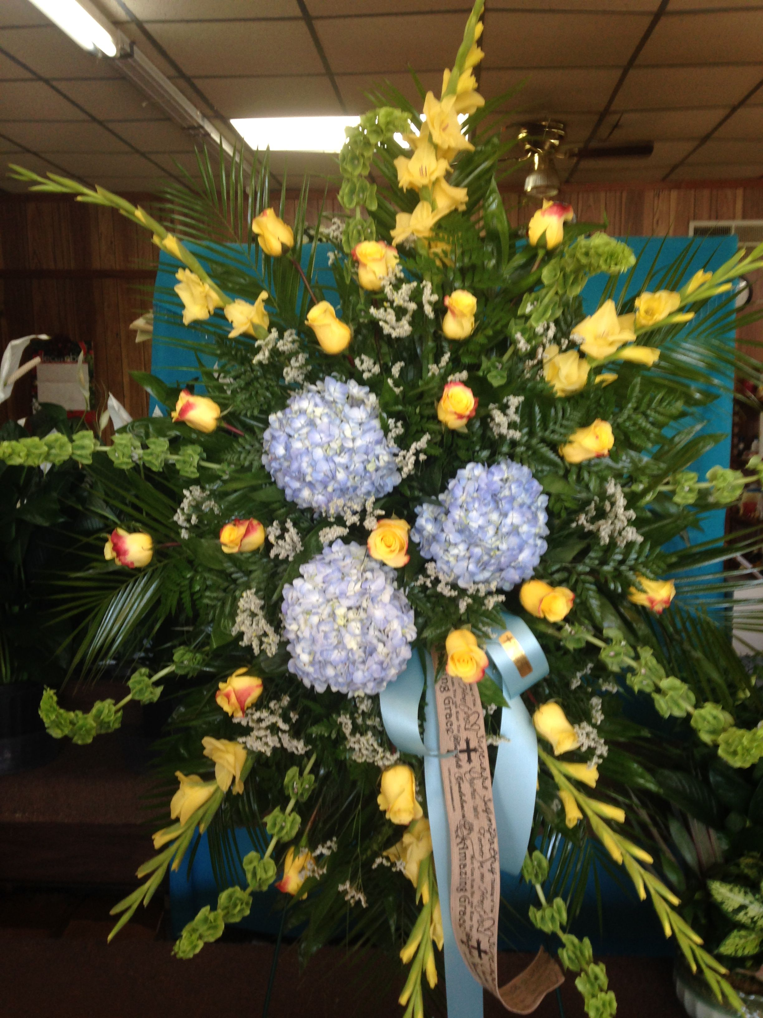 Fresh Funeral Spray Using Blue Hydrangeas Yellow Gladiolus Bells Of Ireland Red Tipped Yellow Roses And White Flowers For You Funeral Sprays Blue Hydrangea