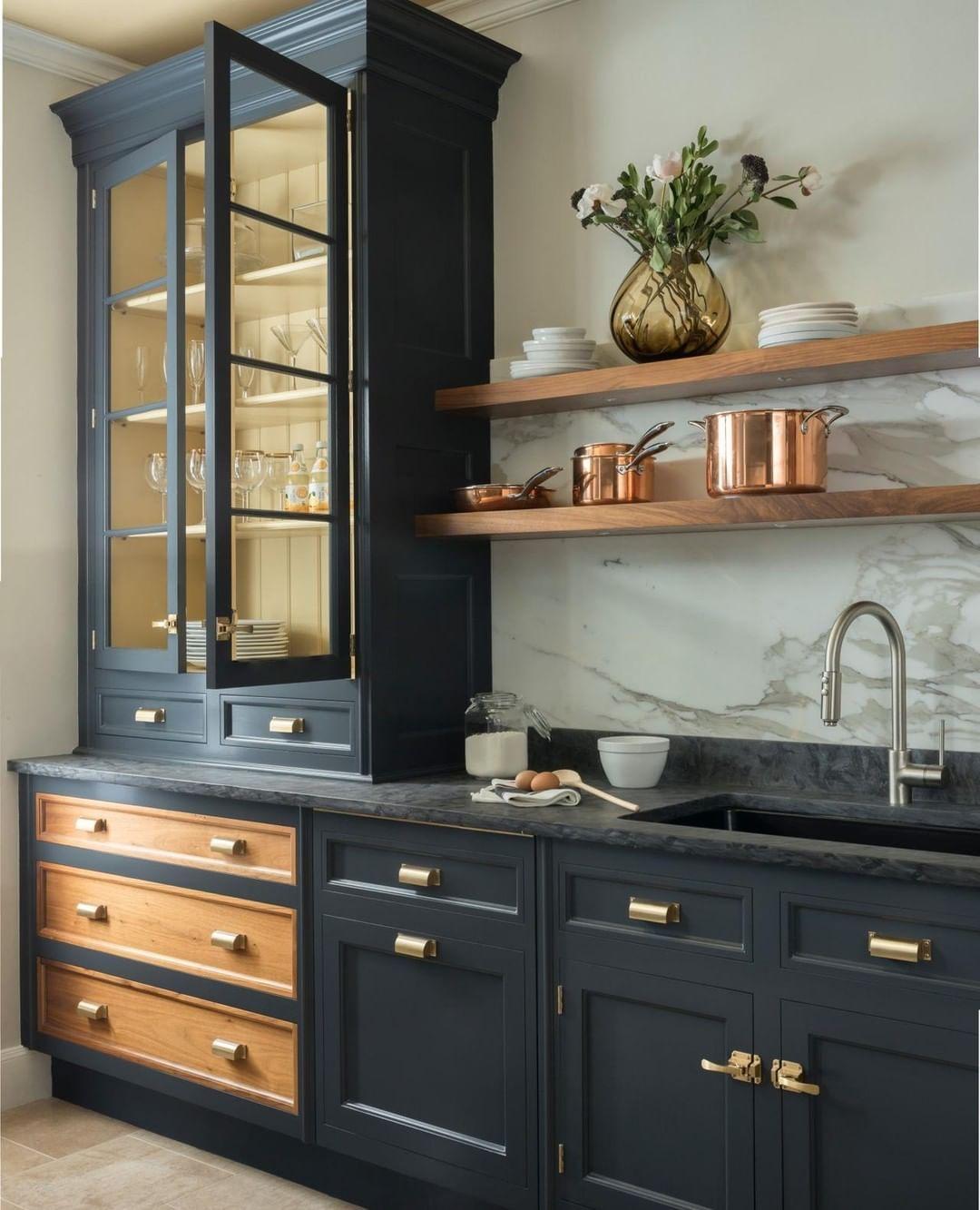 Dark kitchen cabinets, open shelves, brass hardware, and a ...