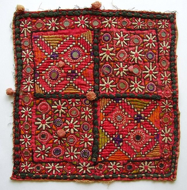 "Afghan Embroidery. ""Two squares of stylized floral motifs and mirrors and two squares of ribbed geometric designs and two mirrors bisected by loose braid of black thread held in place by red thread, similar black braid around edge. Border of floral motifs and mirrors. Small round loose tufts of pink in center of squares and spaced around edges. Baluch design."""