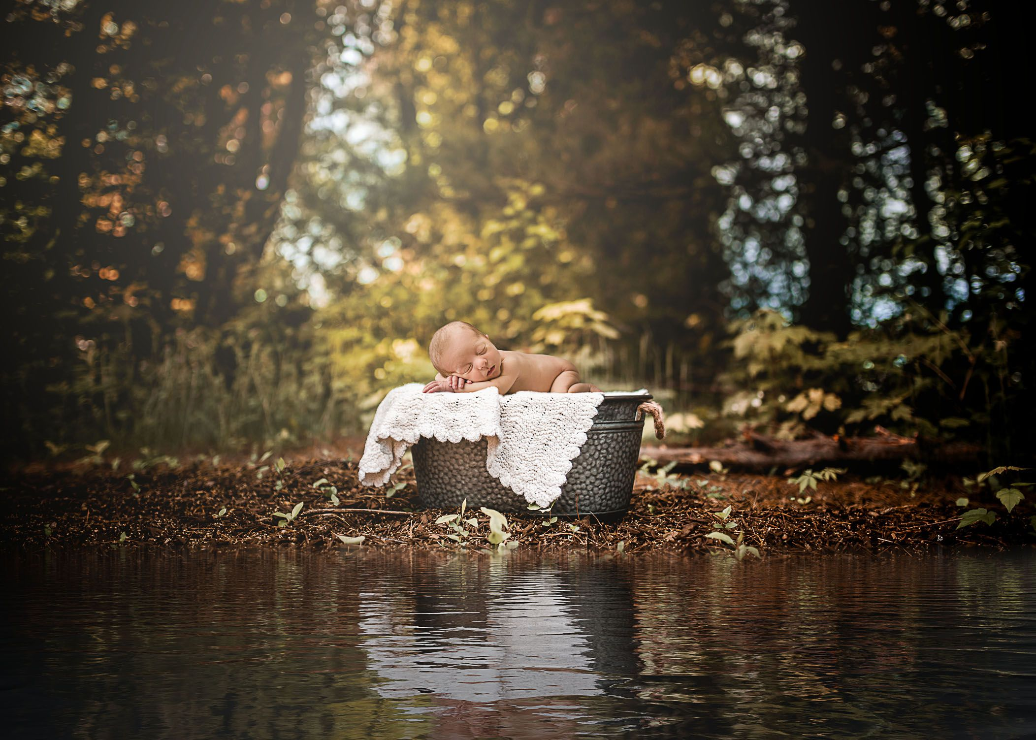 Newborn baby sleeping in a wash bucket near a small pond | One Big ...