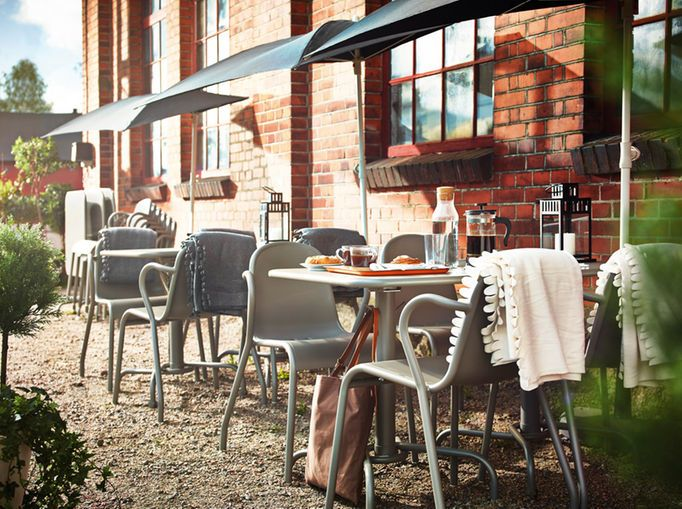 An Outdoor Bistro With Grey Stackable Armchairs And Foldable Tables.  Combined With Black Parasols And Nice Ideas