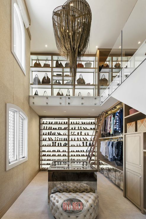 Two Story Closet Boasts An Intermixed Chandelier Hanging Over A Mirrored Island With Clear Display