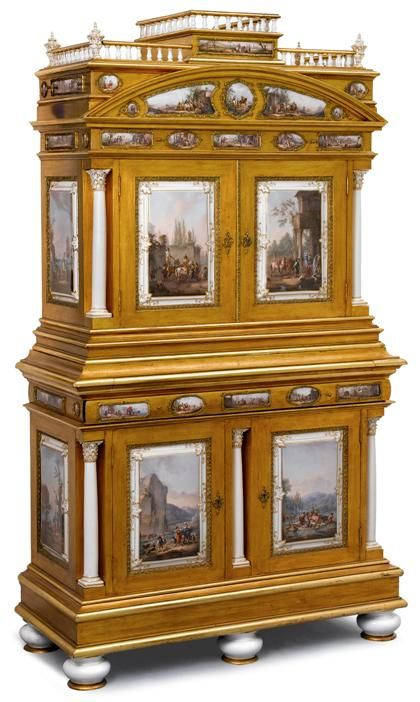 Very fine gilt metal mounted Meissen porcelain and gilt metal mounted giltwood secretaire cabinet circa 1880 Of architectural form and in two sections, the tiered top with baluster gallery, one single short drawer and two drawers to the sides, above long frieze drawer, and two panelled cupboard doors flanked by two full porcelain columns, opening to a long drawer over a secret four-sided rotating unit comprising a bank of three drawers,