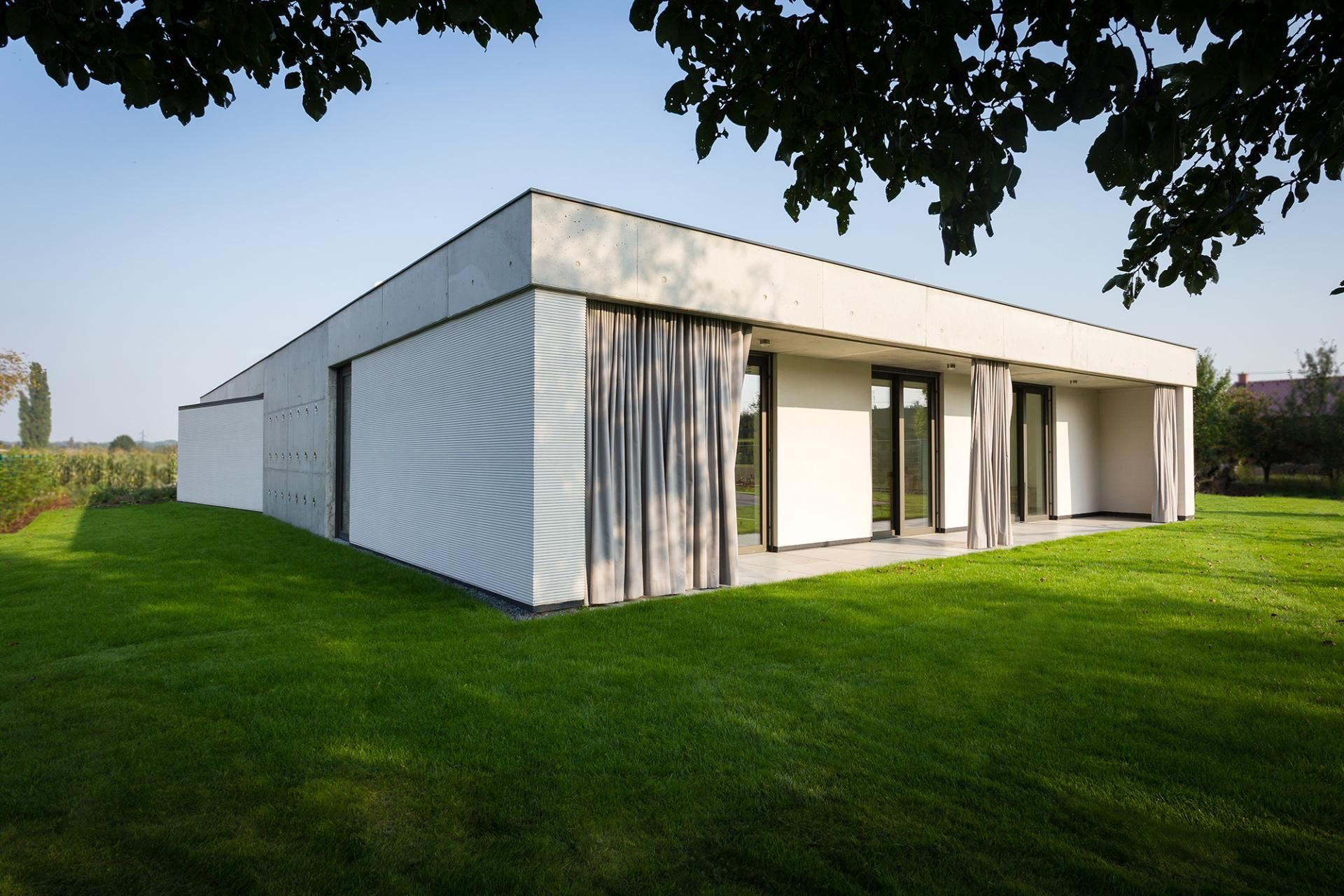 JVArchitekt designed this modern home in Olomouc-Slavonin, Czech Republic, for a family whose main request was for a high level of privacy. The project team developed this contemporary residence with three wings, which create a U-shaped floor plan that faces south, and an inner atrium.