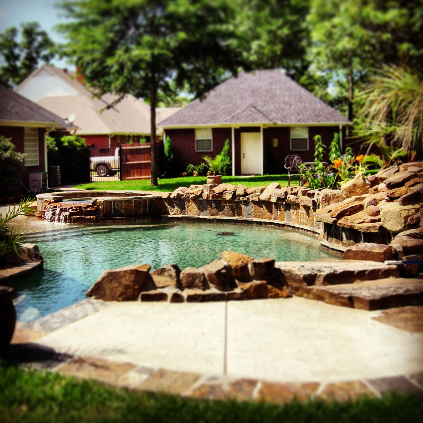 Lagoon style radius gunite pool custom designed and constructed by Preferred Pools; with spa hot tub and waterfall water feature.
