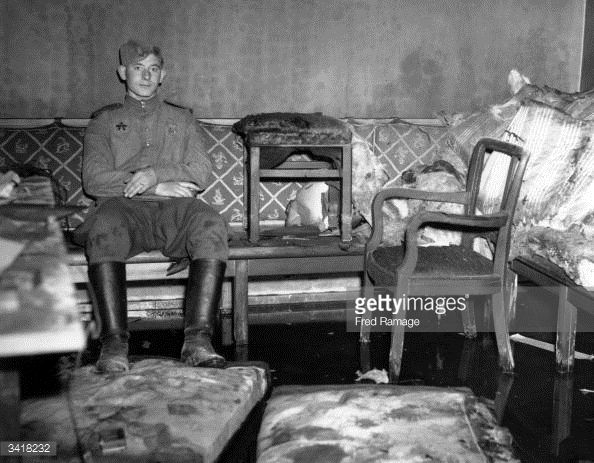 A russian soldier sitting on the sofa upon which german for American sofa berlin