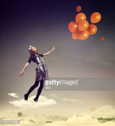 Stock Photo : Girl flying in the air with balloons